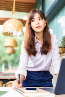 Happy young attractive asian business woman standing while working on her computer at an outdoor patio outside of her office
