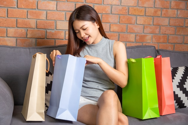 Happy young attractive asian woman in casual clothes looking at merchandises in her shopping bags