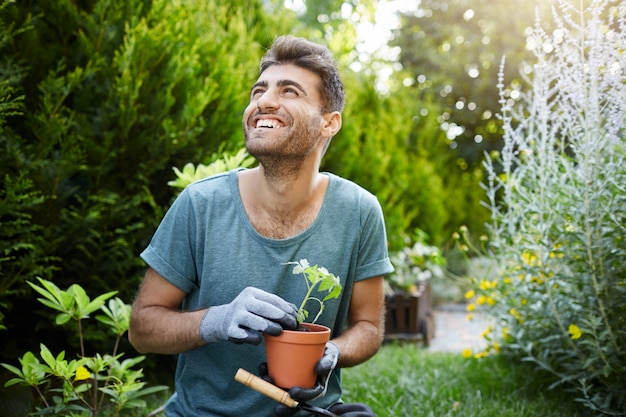 Happy young attractive bearded caucasian male gardener in blue t-shirt and gloves smiling, holding flower pot with green sprout in hands, looking aside with excited face expression