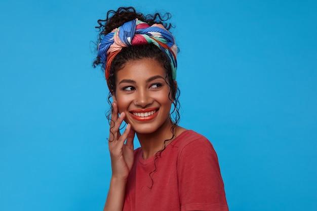 Счастливая молодая привлекательная шатенка кудрявая женщина с праздничным макияжем, касаясь ее лица поднятой рукой и счастливо улыбаясь, изолированная на синей стене