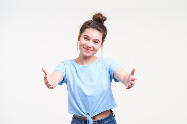 Happy young attractive brown haired woman with bun hairstyle looking positively at front and keeping her hands wide opened while going to give hug someone, isolated over white wall