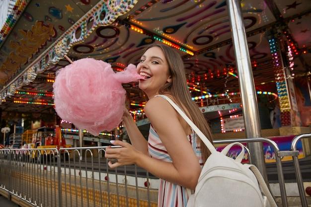 Felice giovane donna bruna attraente con capelli lunghi a piedi attraverso il parco di divertimenti, indossando abiti estivi leggeri e zaino bianco, tirando un pezzo di zucchero filato con i suoi denti