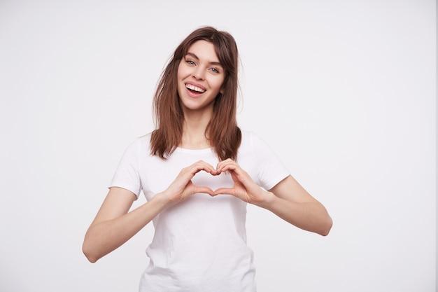 흰색 기본 티셔츠에 흰색 벽 위에 포즈를 취하는 동안 심장 기호로 그녀의 손을 올리고 유쾌하게 웃고 자연스러운 메이크업으로 행복 한 젊은 매력적인 갈색 머리 아가씨