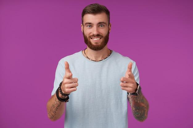 행복 한 젊은 매력적인 갈색 머리 남자 수염을 유쾌 하 고 웃 고, 엄지 손가락으로 손을 올리고 보라색에 고립 된 그의 즐거운 감정을 보여주는