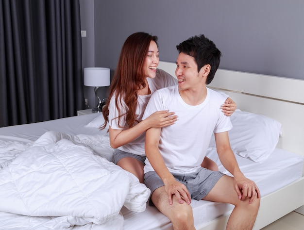 Happy young attractive couple hugging on bed in bedroom