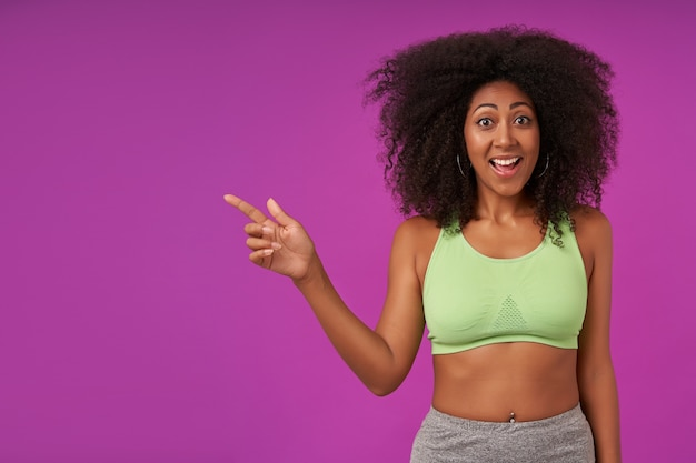 幸せな若い魅力的な暗い肌の女性は、薄緑色のトップを身に着けているカール、陽気な広い笑顔で人差し指を脇に向け、紫色の上に立っています