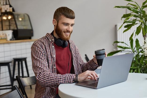 Счастливый молодой привлекательный рыжий бородатый мужчина работает на ноутбуке, сидя в кафе, пьет кофе, одет в основную одежду, широко улыбается и наслаждается работой.