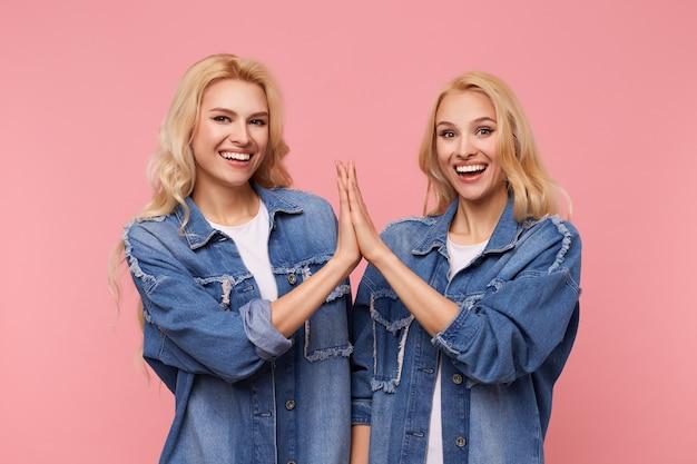 행복 한 젊은 매력적인 긴 머리 금발 자매는 서로 손바닥을 제기 하 고 분홍색 배경 위에 서 카메라에 넓은 미소로 찾고 박수