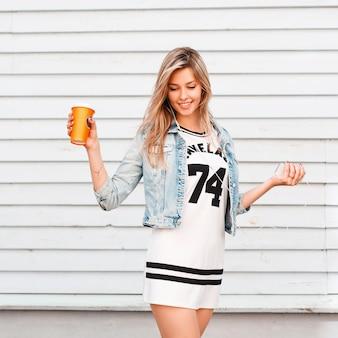 햇살 따뜻한 날에 빈티지 나무 벽 근처 포즈 유행 여름 옷에 행복 한 젊은 매력적인 여자. 매력적인 소녀는 커피를 마시고 주말을 즐깁니다.