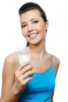彼女の手にミルクのガラスを持つ幸せな若い魅力的な女性