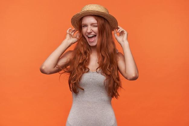 カジュアルな服装でオレンジ色の背景の上に立って、嬉しそうに笑って、上げられた手で彼女のカンカン帽の帽子を保持し、カメラにウィンクを与える波状のセクシーな髪の長い髪の幸せな若い魅力的な女性
