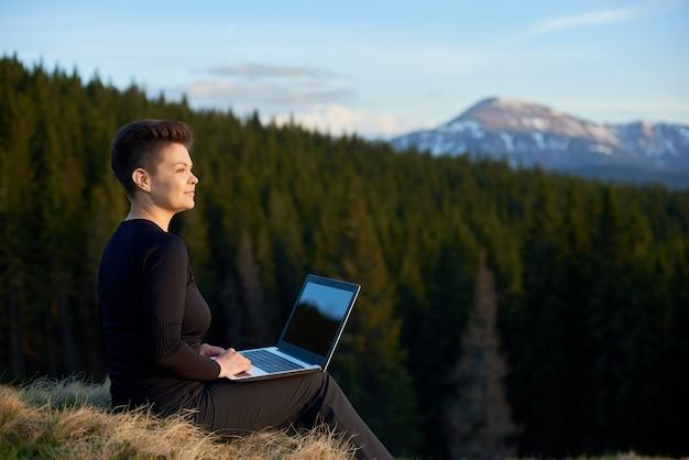 山の景色を楽しみながら彼女のラップトップを屋外で作業して幸せな若い魅力的な女性