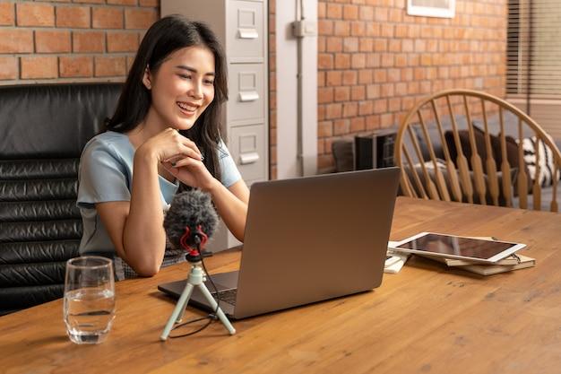 행복 한 젊은 매력적인 여자 작업 또는 그녀의 거실에서 집에서 그녀의 노트북 컴퓨터를 통해 온라인 학습
