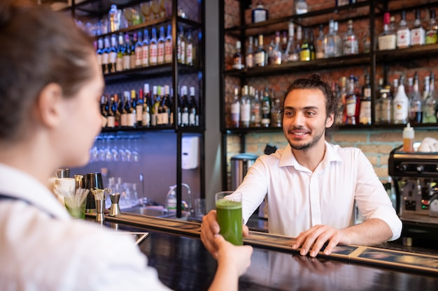 Happy young barman holding glass of vegetable cocktail or smoothie for client while passing it to his colleague over counter