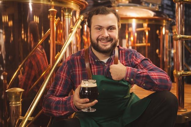 Счастливый молодой бородатый пивовар в фартуке сидит спокойно на своей пивоварне, держа бокал пива, показывает палец вверх