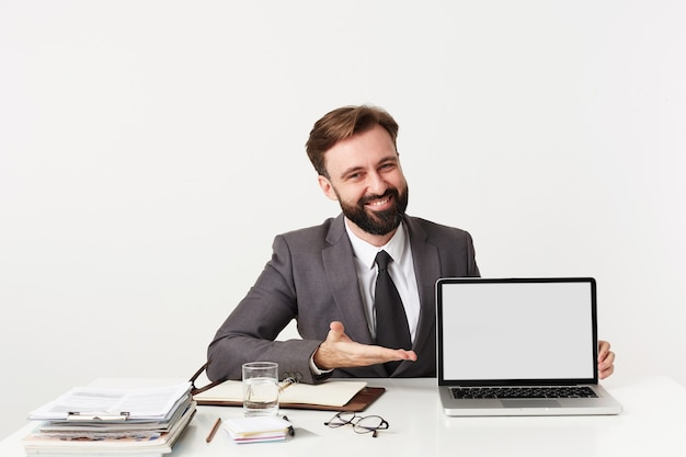 Happy young bearded brunette male with trendy hairstyle having meeting in office and demonstrating something on his laptop, wearing grey suit and tie over white wall