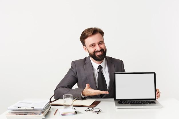 Felice giovane barbuto maschio brunetta con acconciatura alla moda avendo riunione in ufficio e dimostrando qualcosa sul suo computer portatile, indossa un abito grigio e cravatta sopra il muro bianco