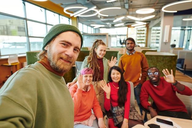 Счастливый молодой бородатый бизнесмен в повседневной одежде, делающий селфи со своими веселыми межкультурными коллегами, сидящими на рабочем месте на фоне