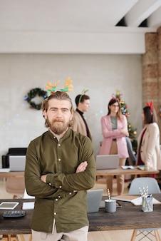 셔츠와 크리스마스 모자를 쓴 행복한 젊은 사업가가 토론을 하는 동료들에 맞서 서서 팔짱을 끼고 있습니다.
