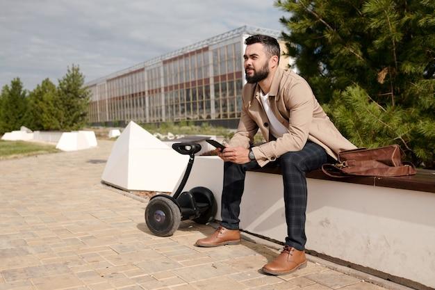 현대 건축에 대한 침엽수 나무에 의해 도시 환경에 앉아 모바일 가제트와 함께 행복 젊은 수염 사업가