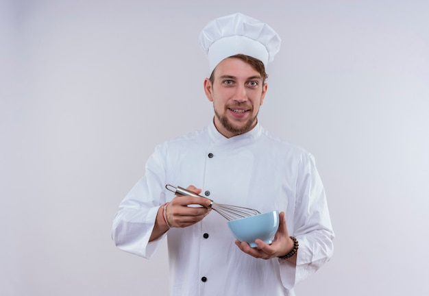 A happy young bearded chef man wearing white cooker uniform and hat holding blue bowl with mixer spoon while looking on a white wall