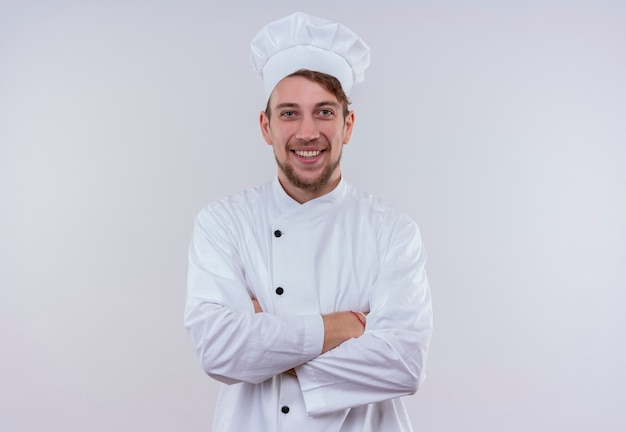 A happy young bearded chef man wearing white cooker uniform and hat smiling and holding hands folded while looking on a white wall