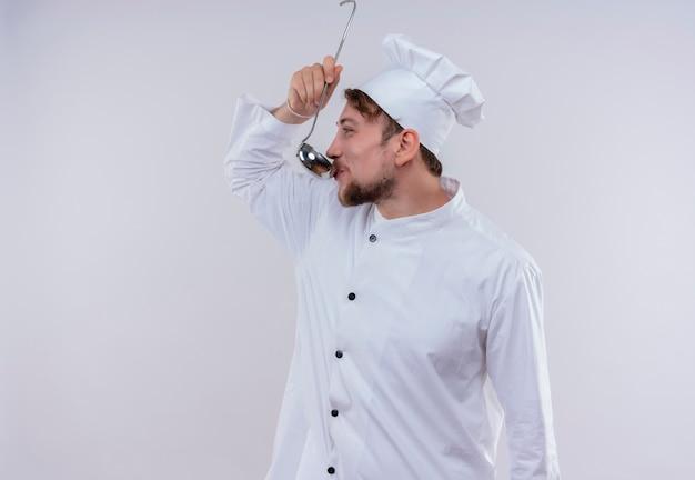 Un giovane uomo barbuto felice del cuoco unico che indossa l'uniforme bianca del fornello e la minestra dell'assaggio del cappello dal mestolo su una parete bianca