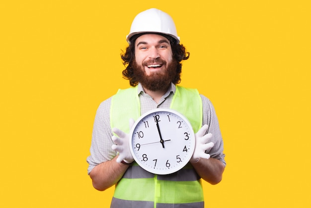 Happy young bearded engineer is holding a big rounded clock and smiling is looking at the camera near a yellow wall