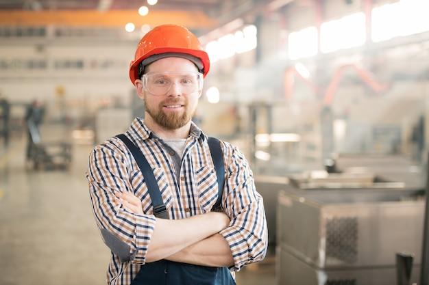 Happy young bearded engineer in protective helmet