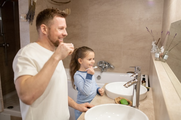 Happy young bearded father and his cute little cheerful daughter holding toothbrushes by their teeth while standing in bathroom