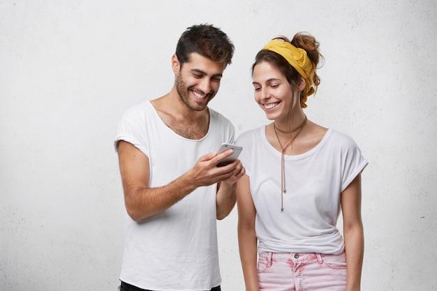 幸せな若いひげを生やしたヒップスタースマートフォンを保持している彼のガールフレンドの面白い写真やビデオを示します。電子デバイスで高速インターネット接続を一緒に使用してリラックスしたのんきなヨーロッパのカップル