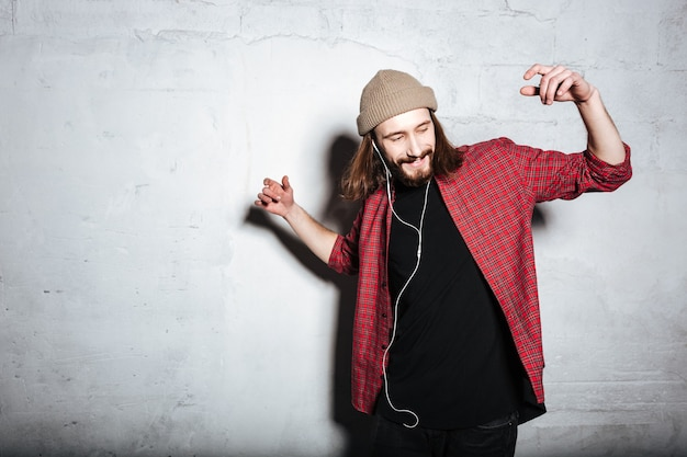 Happy young bearded hipster man wearing hat dressed in shirt in a cage isolated over wall while listening music with earphones