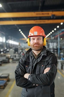 Happy young bearded industrial worker in protective headphones and helmet posing