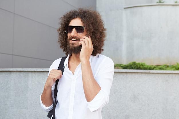 Felice giovane maschio barbuto camminando per strada e parlando al telefono, indossando occhiali da sole e abiti casual, essendo allegro e contento