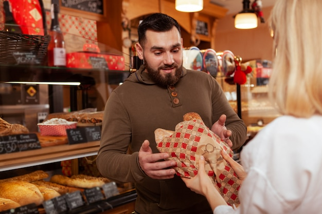 Happy young bearded man buying delicious fresh bread from the baker