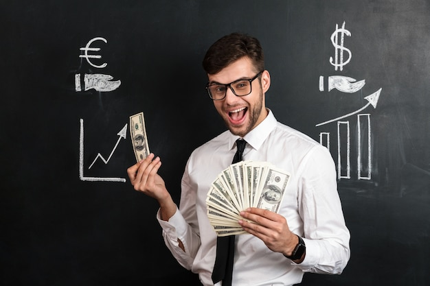 Happy young bearded man in glasses holding bunch of money