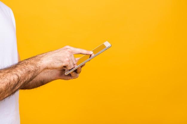 Счастливый молодой бородатый человек в случайном положении и с помощью планшета, изолированных на желтом фоне. крупный план.