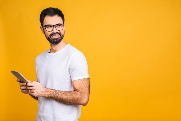 Счастливый молодой бородатый человек в случайном положении и с помощью планшета, изолированных на желтом фоне.