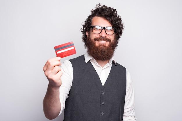 白の彼の新しいデビットカードを示すスーツを着た幸せな若いひげを生やした男。