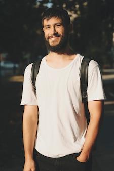 バックパックを背負って、日光の下で立っているカメラに笑みを浮かべて白いtシャツで幸せな若いひげを生やした男