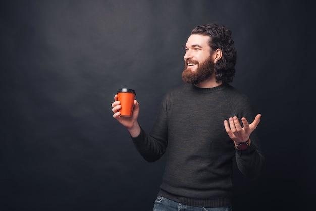 幸せな若いひげを生やした男は笑顔が目をそらしているホットドリンクのカップを保持しています