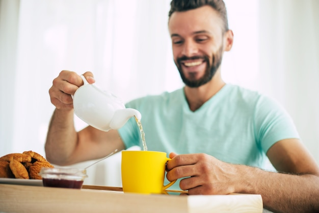 Happy young bearded man is sitting on his bed and has his breakfast with tea or coffee