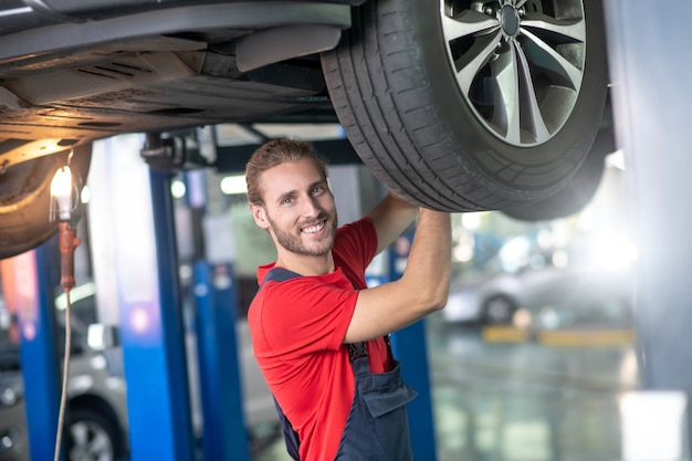 Happy young bearded man in overalls standing under raised car working near wheel