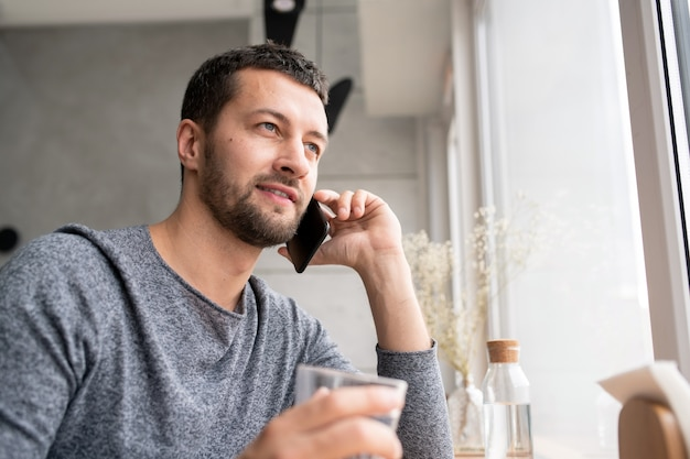 Happy young bearded man in pullover communicating to someone on mobile phone while relaxing in cafe