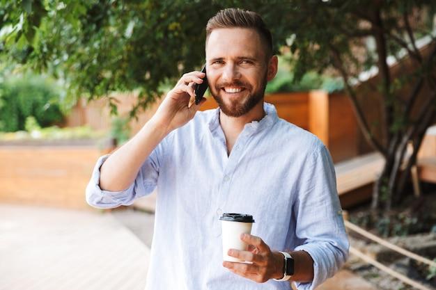 携帯電話で話している幸せな若いひげを生やした男