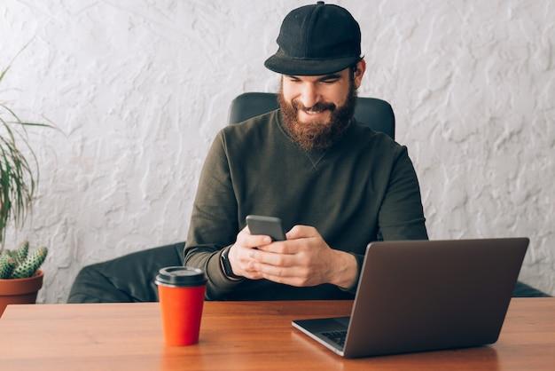 彼のスマートフォンを使用して、オフィスに座っている幸せな若いひげを生やした男