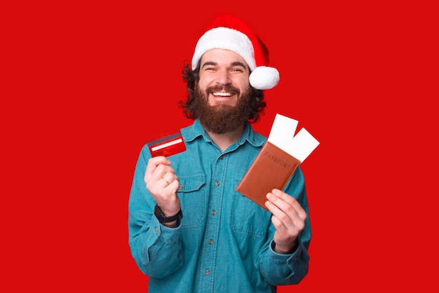 Happy young bearded man wearing santa claus hat and showing red credit card and passport with airplane tickets