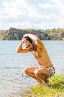 Happy young bearded man wetting hair on lake