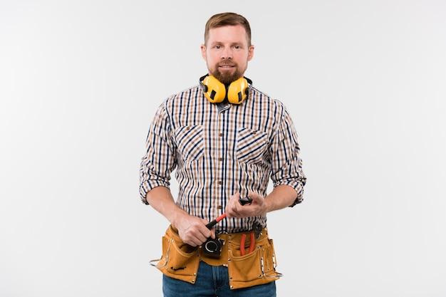 保護イヤホン、ハンマー、カメラの前に単独でツールベルト立って幸せな若いひげを生やした修理