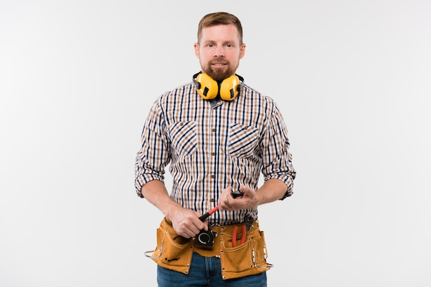 Happy young bearded repairman with protective earphones, hammer and tool belt standing in front of camera in isolation